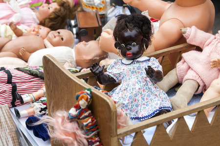 second hand: Second hand dolls at a jumble sale in France. Black doll with golden earrings in a wooden crib on the foreground and some white dolls in the background.