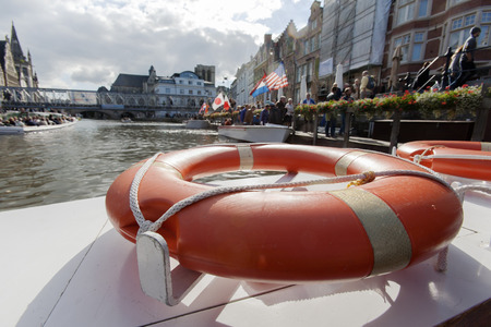 life buoy: Orange life buoy for safety on a boat in Ghent, in Belgium
