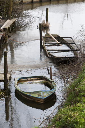 sunken boat: Two small boats filled with rainwater at the end of winter