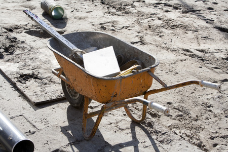leveling instrument: Orange wheelbarrow with tools on a construction site Stock Photo