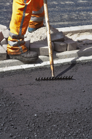 leveling: Manual worker resting after leveling new asphalt with a rake Stock Photo