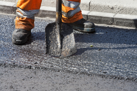 asphalt paving: Manual worker with his shovel asphalt Stock Photo