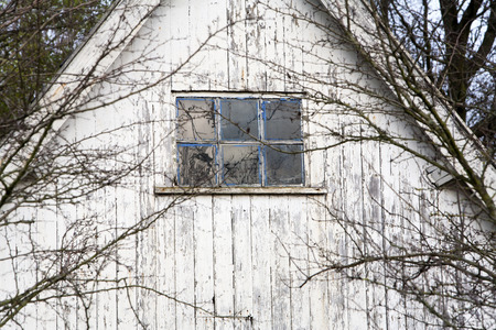 log cabin winter: Weathered window of an old white wooden barn Stock Photo