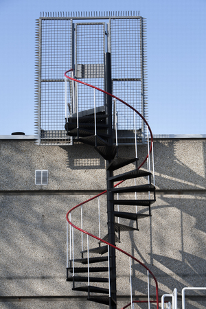 bannister: Emergency exit with metal spiral staircase in the Netherlands. A fence and door with lock is placed against burglars. Hopefully it is easy to unlock in case of fire. There are always a problems between security and safety. Stock Photo