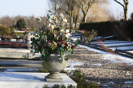 Artificial flowers on a grave at a cemetery in the Netherlands Stock Photo