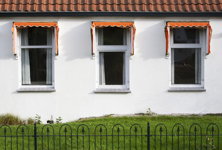 awnings windows: Three windows with orange awnings, a small garden and roof tiles. A typical dutch house.