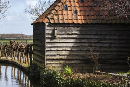 dutch culture: Old roof tile barn  with a birdhouse next to the water