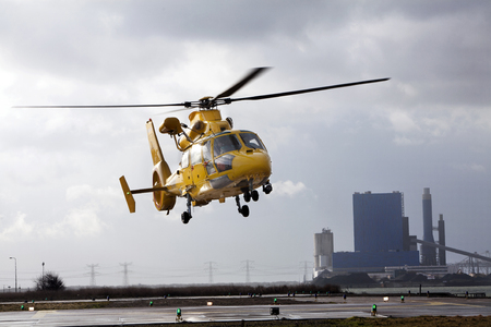 helipad: Helicopter leaving the helipad in an industrial area