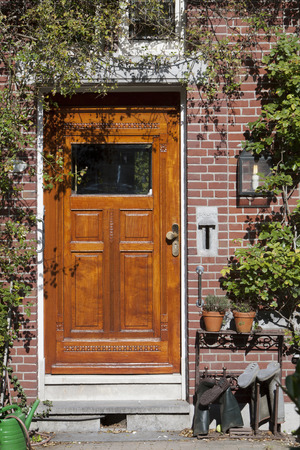 jackboots: Brown wooden door of a brick home with a garden. Jack Boots and watering can next to the door