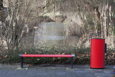 wastepaper basket: Red metal bench and wastepaper basket Stock Photo
