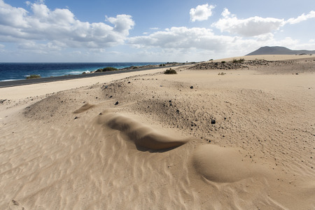 in the sand: The highway along the ocean and sand dunes on Fuerteventura Stock Photo