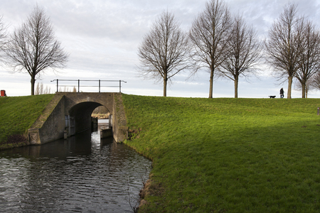 18th century: Dike with 18th century bridge and sluice in Klundert in the Netherlands. On the dike someone is walking the dog Stock Photo