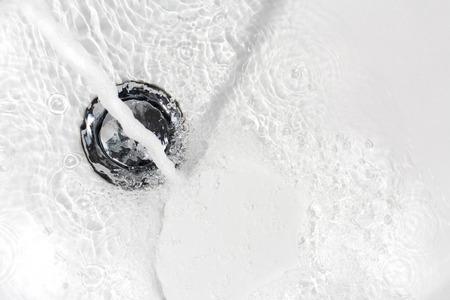 spoiling: Fresh water running down the drain of a ceramic washbasin