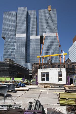 Crane opheffen van een muur op een bouwplaats in Rotterdam met de Rem Koolhaas gebouw op de achtergrond Stockfoto