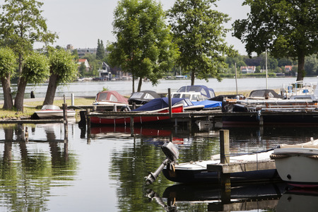 outboard: Boats moored in a small harbor in Rotterdam in the Netherlands. Selective focus on outboard motor. Stock Photo