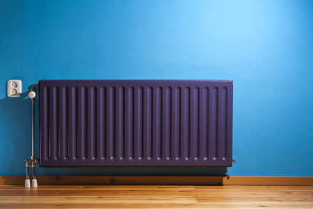 Purple central heating radiator and a blue wall with power point in the Netherlands Stockfoto