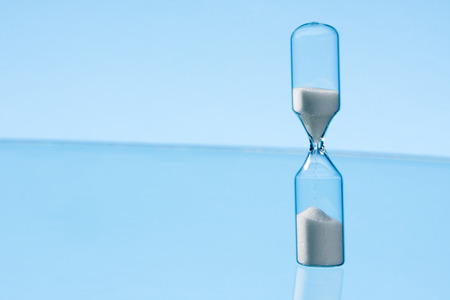 seconds: Hourglass with clean blue background Stock Photo