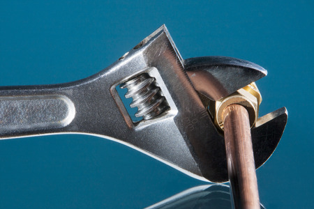 Plumber wrench for repairing a copper water pipe with a blue background