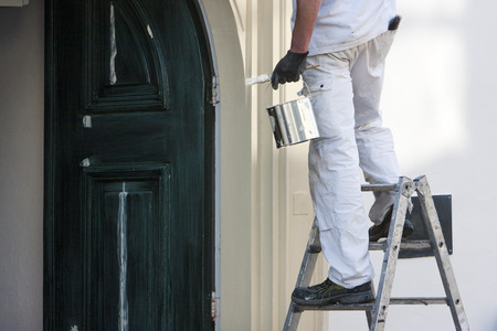 Close-up of a professional house painter with paint and brush