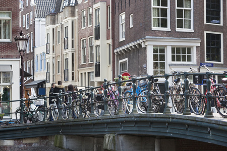 prinsengracht: Bicycles attached to a bridge on the Prinsengracht in Amsterdam Editorial