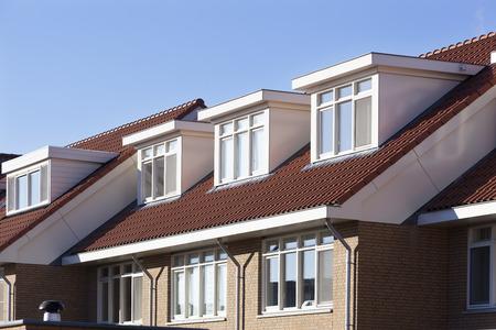 Rode pannen dak met dakkapellen in Nederland Stockfoto