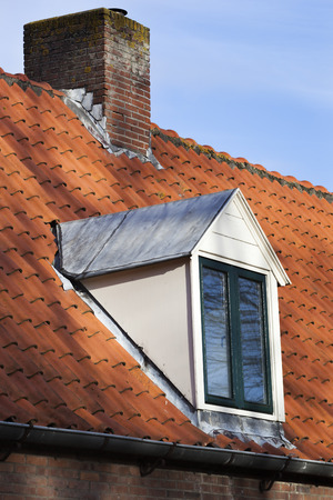 dormer: Old picturesque red tiled roof with dormer and chimney in the Netherlands Stock Photo
