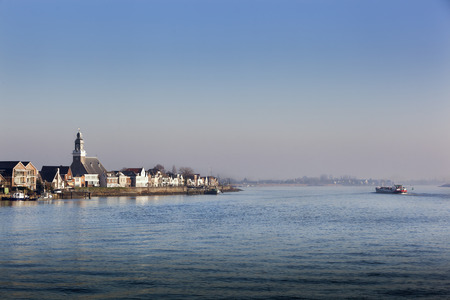 Village Lekkerkerk near the river Lek in the Netherlands. An industrial  ship is passing by. Stock Photo