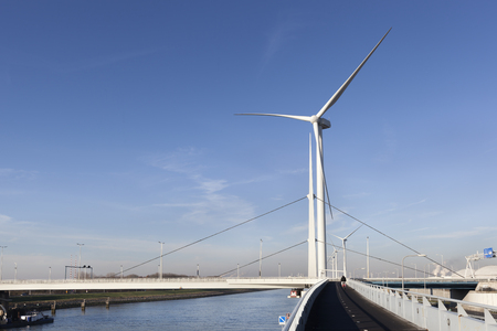 Wind turbines and an asphalted two way bicycle path near canal Hartel in Rotterdam Stock Photo