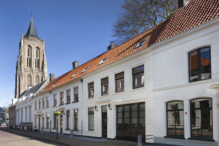 Street with traditional houses and the old church tower in Gorinchem in the Netherlands