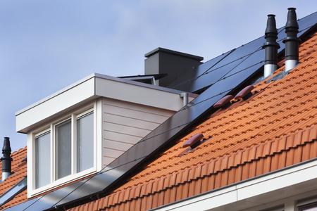 ドーマと赤瓦屋根の上のソーラー パネル