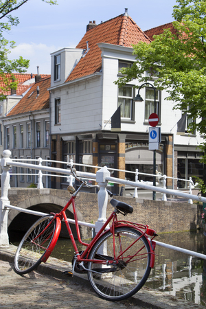Red bicycle near a canal in Delft in the Netherlands