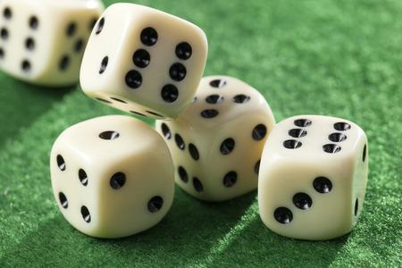 Vijf rollende dobbelstenen in beweging op groen vilt Stockfoto