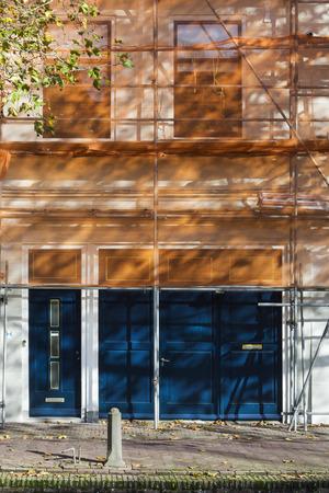 Renovatie van een gebouw in Gouda met steigers en oranje vangnet