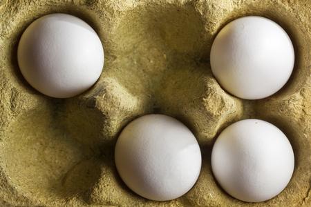Vier witte biologische eieren in een doos bestaande uit 50 procent grasvezels en is volledig recyclebaar