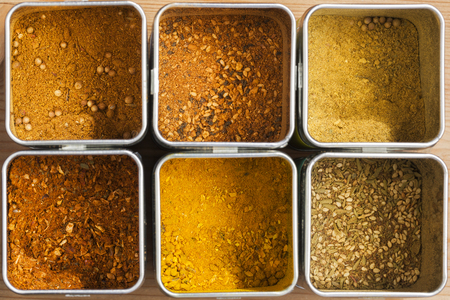 Six different spice mixtures in metal cans seen from above