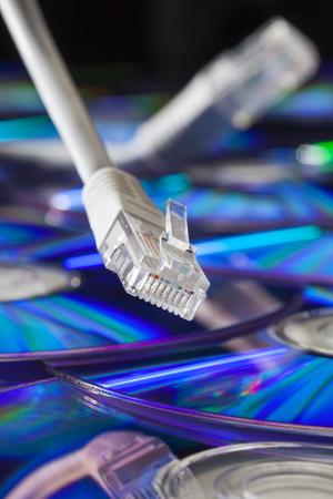 Close-up van een netwerkstop en een kabel met een stapel van cds technische achtergrond Stockfoto