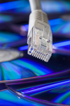 Closeup of a network plug and cable with a pile of cds technical background Stock fotó