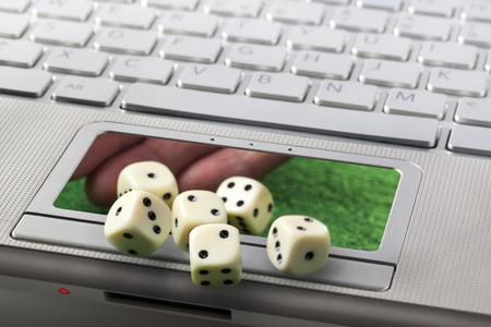 Online gokken of gaming concept met laptop toetsenbord en handwerpen dobbelstenen via de touchpad
