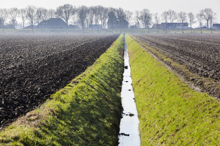 Plowed fields and a ditch  in the Hoeksewaard in the Netherlands 스톡 콘텐츠