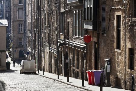Old vintage street with dirty car and colorful garbage bins in Edinburgh