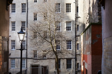Classic lamppost in old town Edinburgh with dirty buildings and an old vintage wall in Edinburgh Stockfoto