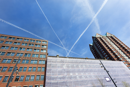 Contemporary buildings and plane stripes in a blue sky in Rotterdam center Stockfoto
