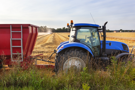 Tractor and trailer with a combine harvesting in the background in Louvemont in France
