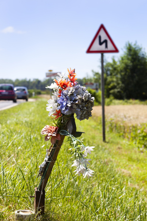 Roadside memorial next to a dangerous bend sign in France Stockfoto