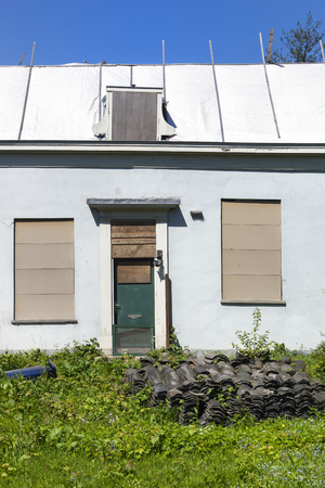 Renovation of an old house with a pile of old roof tiles in front Stockfoto