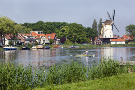 The idyllic river Rotte in Rotterdam with an old white windmill and some houses at the other side while a rowing boat is passing by