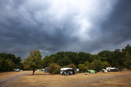 Weather change introduced by dark dramatic rain clouds coming to the camping in Nunpeet in the Netherlands