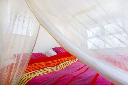 Bed with colorful quilt under a mosquito net Zdjęcie Seryjne