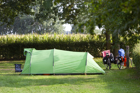 Tent and two bikes on a camping next to a corn field in Voorst in the Netherlands