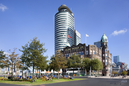 Sunbathing in a beach chair in front of the famous New York hotel on the south bank in Rotterdam